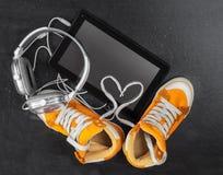 Espadrilles oranges, écouteurs, comprimé Photos stock