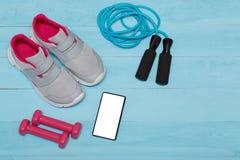 Espadrilles, poids, téléphone et une corde de saut sur le fond bleu Photos libres de droits