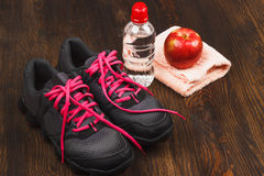 Espadrilles, pomme et bouteille de l'eau Photo stock