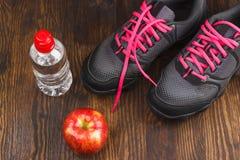 Espadrilles, pomme et bouteille de l'eau Image libre de droits