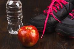 Espadrilles, pomme et bouteille de l'eau, fond en bois Photos libres de droits