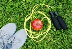 Espadrilles, pomme et corde à sauter sur l'herbe verte fraîche Photo stock