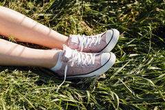 Espadrilles pourpres sur des jambes de fille à l'herbe Image libre de droits