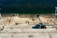 Espadrilles près de l'eau sur la plage Photographie stock