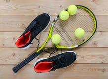 Espadrilles, raquettes et boules de tennis sur la table en bois Photographie stock