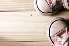 Espadrilles roses de fille sur un plancher en bois Images stock