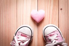 Espadrilles roses du ` s de fille avec les coeurs roses sur un plancher en bois Photographie stock libre de droits