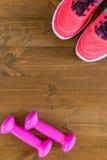 espadrilles roses et une haltère dans les coins du cadre Images stock