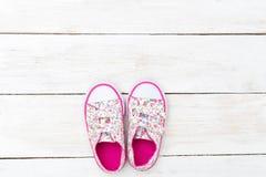 Espadrilles roses pour la petite fille sur le fond en bois blanc l plat Photo stock