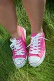 Espadrilles roses sur des pattes de fille sur l'herbe Photos stock