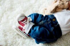 Espadrilles rouges à la mode sur de petits pieds nouveau-nés de bébés garçon Photographie stock