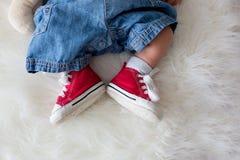 Espadrilles rouges à la mode sur de petits pieds nouveau-nés de bébés garçon Images stock