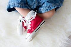 Espadrilles rouges à la mode sur de petits pieds nouveau-nés de bébés garçon Photo libre de droits