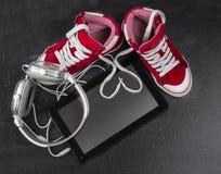 Espadrilles rouges, écouteurs, comprimé Photographie stock