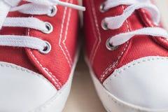 Espadrilles rouges de bébé en gros plan Photographie stock libre de droits