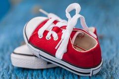 Espadrilles rouges de bébé sur le fond bleu en bois Image stock