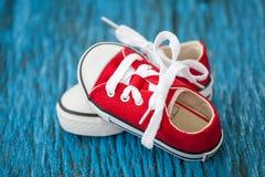 Espadrilles rouges de bébé sur le fond en bois bleu Photos stock