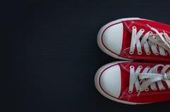 Espadrilles rouges de la jeunesse de textile sur une surface en bois noire Photographie stock libre de droits