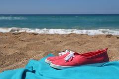 Espadrilles rouges et couverture bleue sur la belle plage Images stock