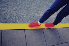 Espadrilles rouges sur la ligne jaune de route Photos libres de droits
