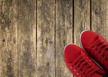 Espadrilles rouges sur la plate-forme en bois Photos stock