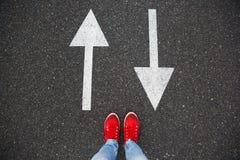 Espadrilles rouges sur la route goudronnée avec les flèches tirées indiquant deux directions Image libre de droits