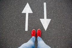 Espadrilles rouges sur la route goudronnée avec les flèches tirées indiquant deux directions Photographie stock libre de droits