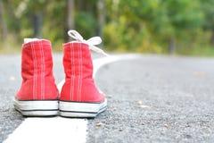 Espadrilles rouges sur le fond de route Images stock