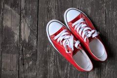 Espadrilles rouges sur le fond en bois Le concept du sport, établissent, T Photo libre de droits