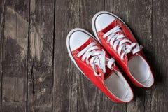 Espadrilles rouges sur le fond en bois Le concept du sport, établissent, T Photos libres de droits