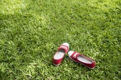 Espadrilles rouges sur les herbes vertes Image libre de droits