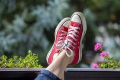 Espadrilles rouges sur les jambes d'une femme dans la perspective de nature Photo stock