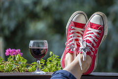 Espadrilles rouges sur les jambes d'une femme et d'un verre de vin dans la perspective de nature Photos stock
