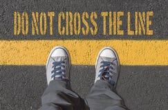 Espadrilles se tenant sur la ligne jaune Image libre de droits