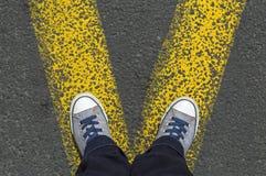 Espadrilles se tenant sur la ligne jaune Photos libres de droits