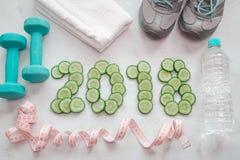 Espadrilles, serviette, eau et haltères Symbole découpé en tranches par concombre de Images stock
