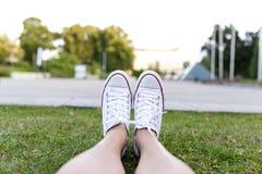 Espadrilles sur l'herbe verte en parc de ville Images stock