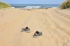 Espadrilles sur l'océan de plage de route de sable Image libre de droits