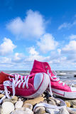 Espadrilles sur la plage pierreuse Photos stock