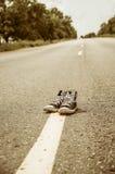 Espadrilles sur la route Photographie stock libre de droits