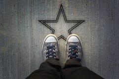 Espadrilles sur la route avec la forme d'étoile Photos libres de droits