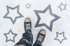 Espadrilles sur la route avec l'empreinte de forme d'étoile Photos libres de droits