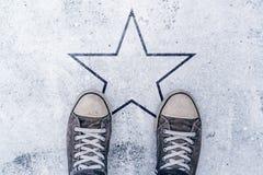 Espadrilles sur la route avec l'empreinte de forme d'étoile Photographie stock