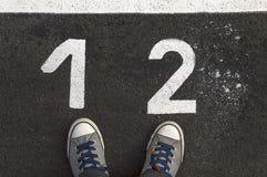 Espadrilles sur la route goudronnée avec le nombre 1 et 2 Photos libres de droits