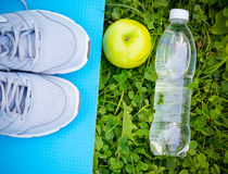 Espadrilles sur le tapis de yoga, la bouteille de l'eau et la pomme sur l'herbe verte fraîche Image stock