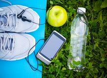 Espadrilles sur le tapis et le smartphone de yoga avec les écouteurs et la pomme Photographie stock libre de droits
