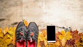 Espadrilles sur les feuilles d'automne, le téléphone portable et l'écouteur Photo libre de droits