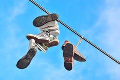 Espadrilles sur les lignes électriques et le ciel bleu lumineux Photographie stock libre de droits