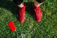 Espadrilles, téléphone et baladeurs rouges sur l'herbe Photographie stock libre de droits