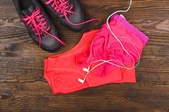 Espadrilles, T-shirt, soutien-gorge de sports et écouteurs Photo stock